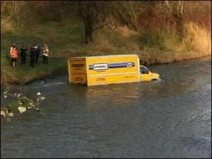 A Freight Van Halfway Submerged in a River